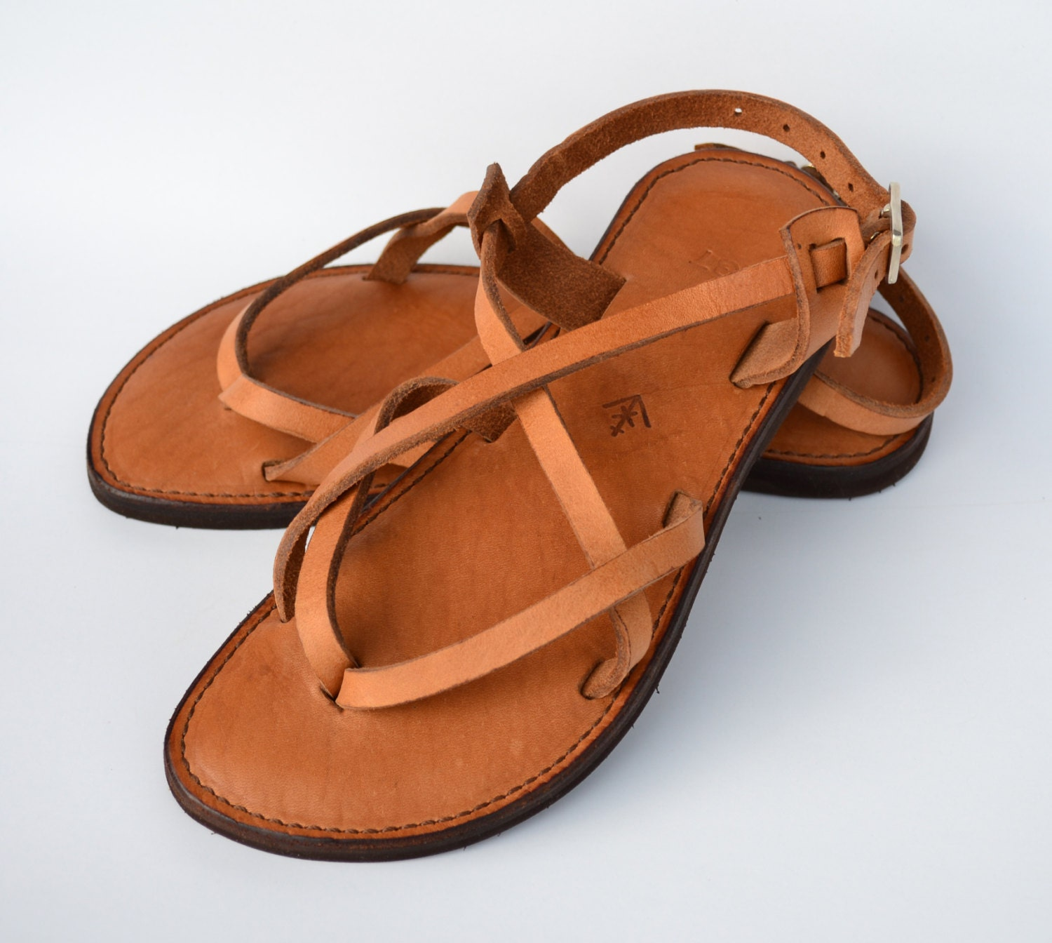 Mens Leather Sandals Warm sun, crashing waves and an ocean breeze—nothing goes better with a relaxing walk on the beach than a good pair of men's leather sandals. Dust off the sand, pull on a pair of linen slacks and a fitted shirt and then take these versatile shoes to dinner.