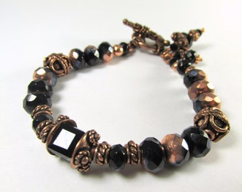 Bracelet in Black and Copper Czech Glass Rondelles Swarovski Cube Center Bead and Bali Style Copper Beads and Toggle Clasp and Charms