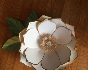 Large white flower with gold edges and bronze gems on each tip, also three shimmering green leaves.
