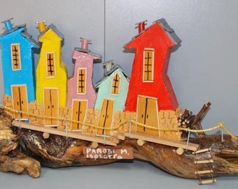 An artistic woodn ornament depicting an imaginary island where the houses are perched.