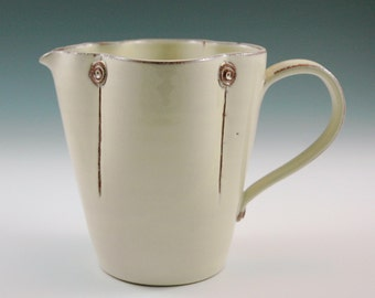 Medium pitcher vanilla colored with straight form.