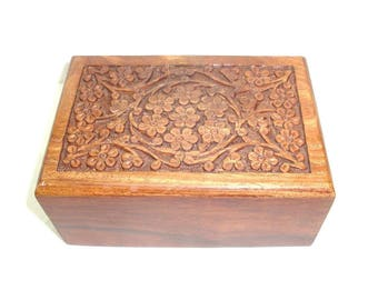 "Carved wooden chest. Unique Box has floral design on the top and a hidden slide opening on the bottom. 6.5"" by 4"" by 2.5"" tall."