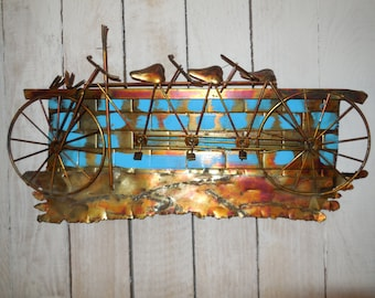 Folk art wall hanging of a bicycle built for three in metals.