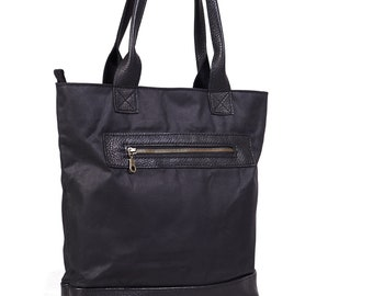 Waxed canvas tote bag with leather handles in black.