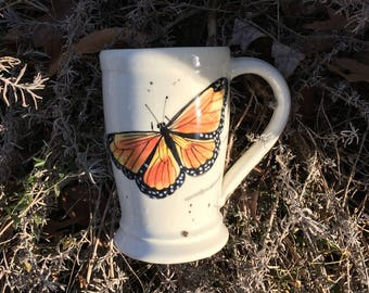 Tall, mug with beautiful Monarch butterfly handpainted and wheel thrown .  Holds 16 plus oz.