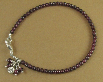 Red garnet bracelet with dangles and charm. Fine and sterling silver.