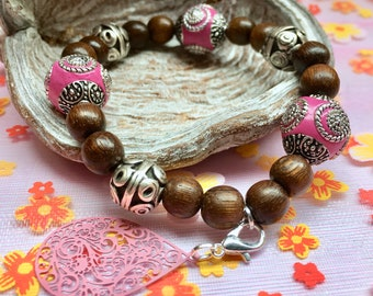 Beaded bracelet with pink elements and charm