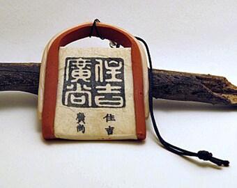 Ornament. Hanging Asian style small decoration. Unique rustic style ornament in ecru and terracotta colours. Small ornament.