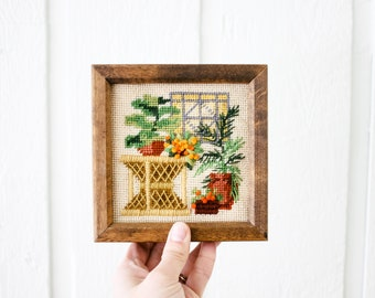 Vintage needlepoint crewel rattan table with plants fiddle leaf fig orange and yellow flowers Norfolk pine wooden framed fiber art 1981