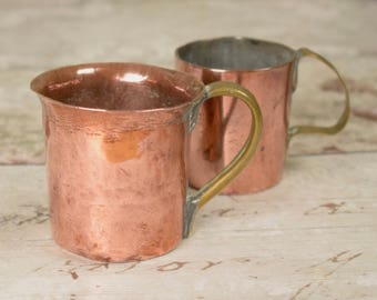 Pair of small vintage copper measures or cups, weathered and worn
