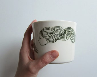 Unique handmade white porcelain cup with a long haired girl illustration, for snacks, desserts and all kind of beverages.