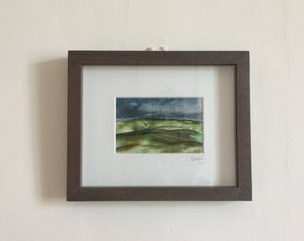 Framed Encaustic wax art landscape in frame, countryside rolling hills and moody grey sky.