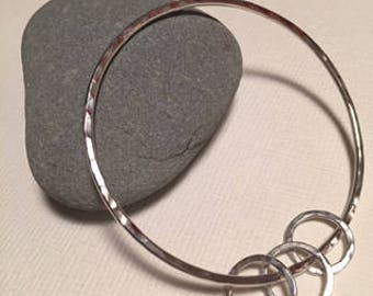 Hammered Sterling Silver stacking bangle, with three hammered silver rings on.