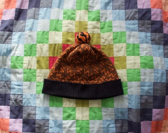 Colourful geometric knitted 'Pivot' design hat with pom-pom. Navy and orange lambswool hat.
