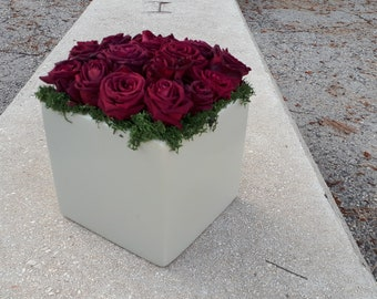 Freeze dried rose arrangement in a ceramic vase with moss.