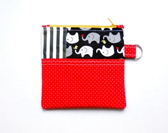 Small patchworked coin purse/zipper pouch with black and white stripes, elephants on black, and red with white dots, with a yellow zip