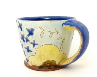 Floral yellow and blue mug. Wheel thrown earthenware mug. Handmade by Kaitlyn Brennan/Brennan pottery in Ottawa Ontario