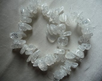Bead mix, ice flake quartz (dyed/heated), white, medium-large chips. Sold per 15 inch strand. There are 77 beads on the strand.