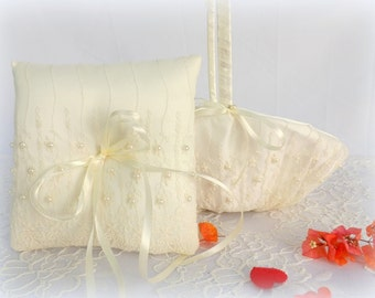 Ivory flower girl basket and wedding ring pillow decorated with floral lace and Ivory pearls.
