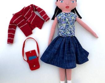 Poupée de fille de l'école avec une mauviette de laine cartable