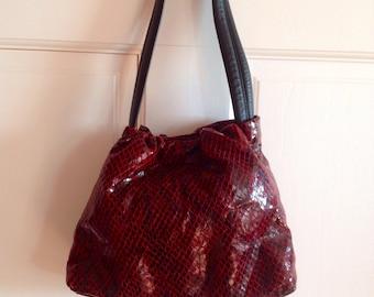 Handbag in red, embossed snakeskin leather designed by Andrew Marc