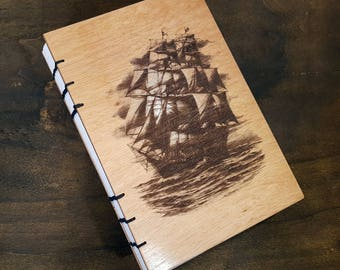Nautical themed notebook with ship engraved on wooden cover. Bound with Coptic Stitching.