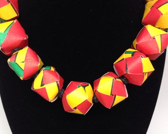 """11 red, yellow and green 3/4""""paper beads are strung on an 18"""" 4mm round black elastic cord with a magnetic clasp."""