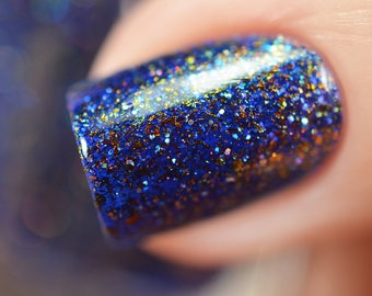 "Nail polish - ""Paper Universe"" A dark royal blue jelly with bronze/gold/green shifting flakes"