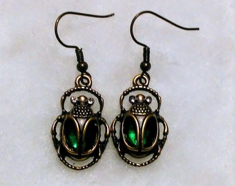 Egyptian scarab beetles in antique gold plated charms with beautiful green glass bodies