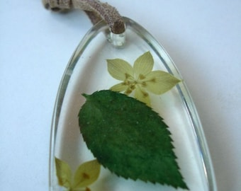 Resin pendant with real flowers and a leaf on a beige cord