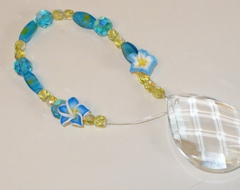 Aqua and yellow crystal suncatcher with a multi-faceted crystal.
