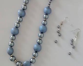 Light gray pearl single strand necklace. Dangle earrings.