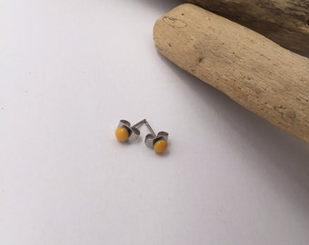 New improved waterproof design! Itty bitty, canary yellow eco-resin studs on allergy-friendly surgical steel.