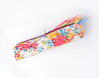 Small pencil case/zipper pouch with flowers in red, yellow and blue on an off-white background and a red zip