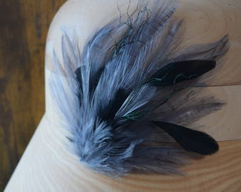 Stunning grey and black feather fascinator. This beautiful headpiece is the perfect hair accessory for a wedding.