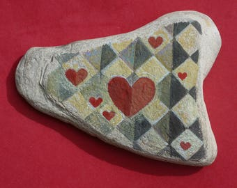 Painted beach rock with hearts and harlequin pattern