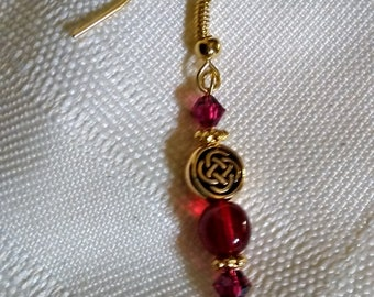 Ruby red and gold plated pierced earrings with Celtic knot beads.
