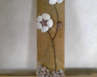 Flower image of shells and stones on wood