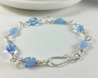 Sterling silver wire wrapped bracelet with light blue glass beads.