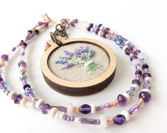 tiny embroidery hoop pendant with hand embroidered lavender flowers on a purple and copper beaded necklace