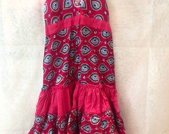 Printed cotton dress for girls. It is regulated and tied with loop. With gum in the back.