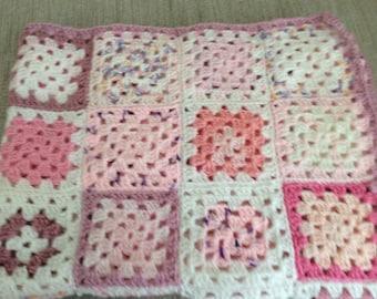 Pink and white crochet pram blanket.