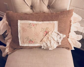 Burlap and linen pillow adorned with vintage fabric squares.