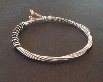 Recycled Guitar String Bracelet/Bangle: Bound with Silver coloured wire.