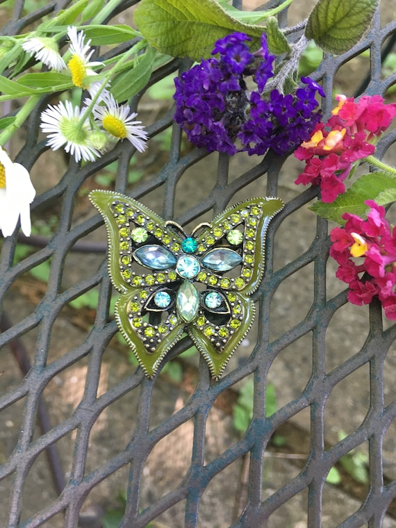 This Elegantly demure Butterfly Brooch is made of Olive Green Enamel with Various Critious Greens  & Aqua Blues Rhinestones in Bronze tone