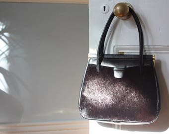 A 1960s, black leather and cow hide handbag in excellent condition.