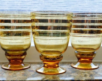 Set of 5 gold and amber glass tumbler / footed glasses. Very pretty with gold trim.