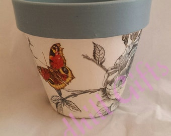 Hand decoupaged plant pot decorated with birds roses and butterflies