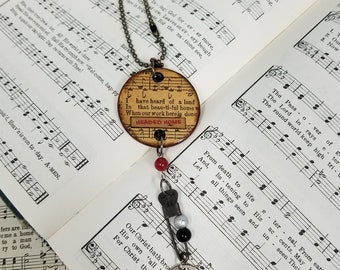 Heartsongs - Never Grow Old is an altered wood poker chip with paper hymn snippets, metal findings and charms