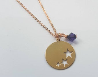 Rose gold colour circular necklace with cut out stars and purple crystal